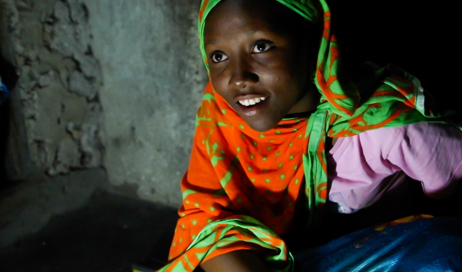 "Fourteen year-old Nuru Sheha studies at night in the light of solar-powered LED lights at home in the village of Matemwe, on the Tanzanian island of Zanzibar. He family's first electrical system was installed by one of Zanzibar's 13 ""solar mamas,"" illiterate women trained in India to be solar power engineers. Able now to study at home for the first time, Nuru's mother says she is doing well in school and wants to be a teacher. Since girls are expected to do house chores during daylight hours, night is the only time they can study. She's doing well in school and dreams of becoming a math and English teacher."
