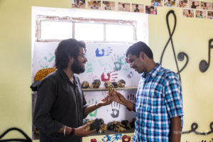 Rajesh being introduced to puppets by Aakash, Education Coordinator
